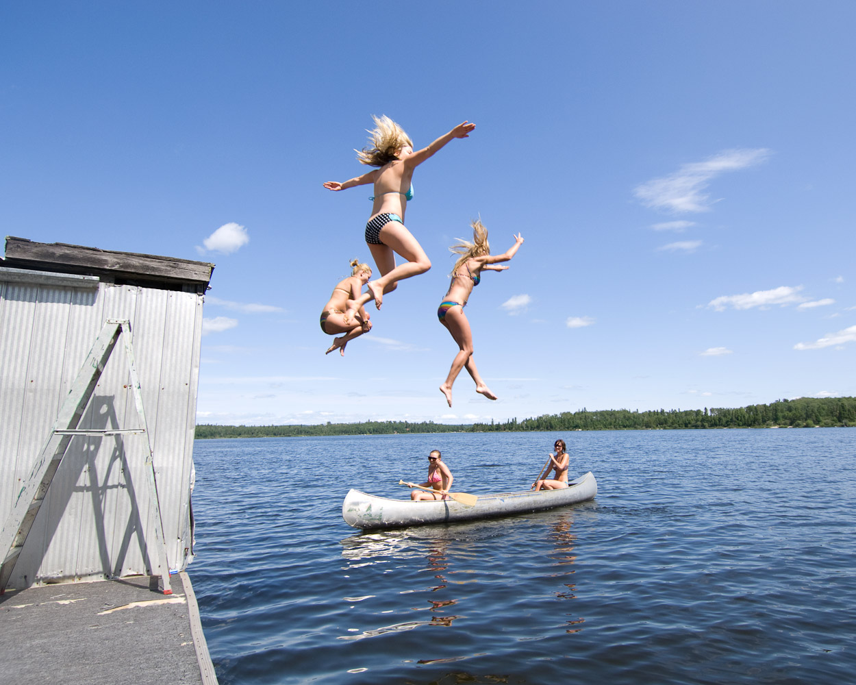 Girls lake jump by Winnipeg editorial photographer